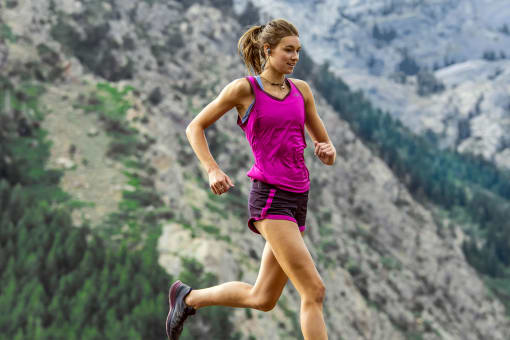A woman trail running while wearing the jaybird X4 outdoor wireless earbuds