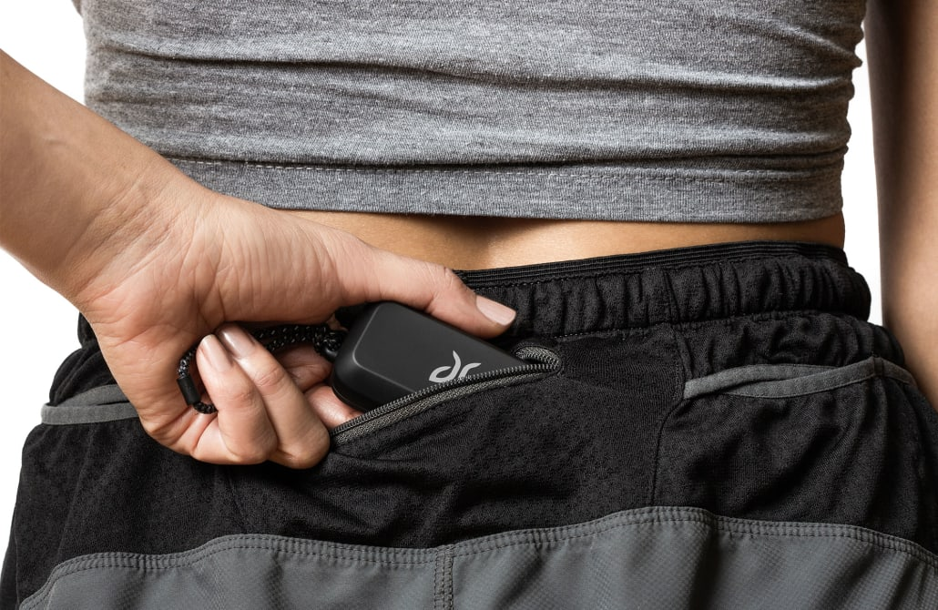 A person storing a small & portable Vista charging case in the back pocket of running shorts