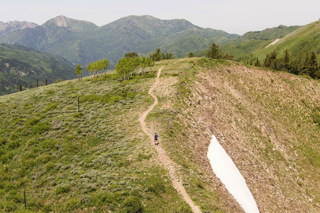 A person trail running while listening to music on the jaybird X4 outdoor wireless earbuds with rapid charge capabilities
